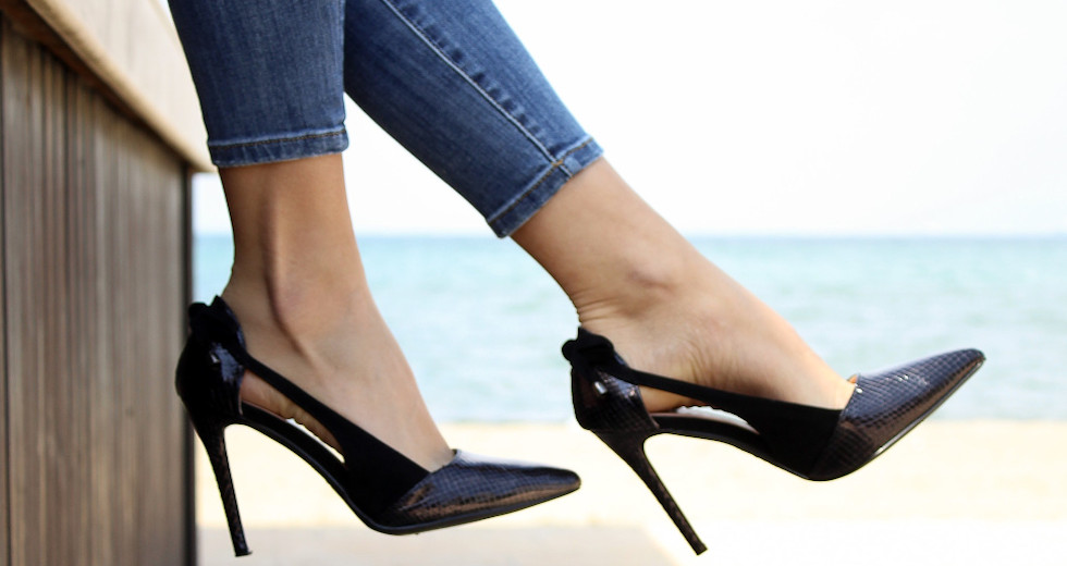Image of a woman's legs and feet dangling over a wall. She is wearing jeans and black high heels